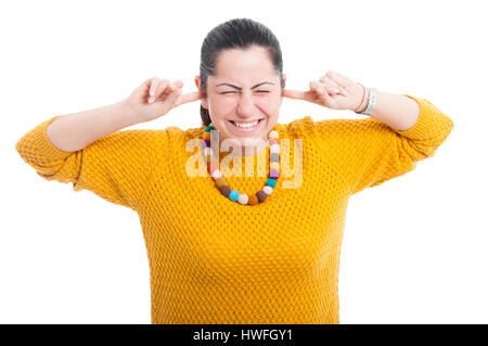 Pretty woman with fingers in ears acting like a deaf on white studio background - Stock Photo