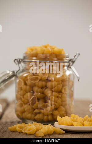 Conchiglie pasta spilling out of jar and spoon on wooden table - Stock Photo