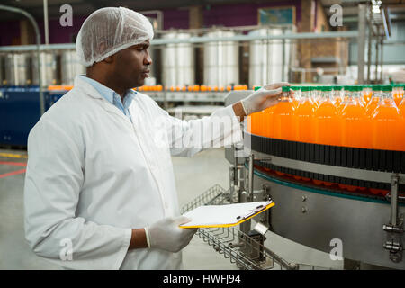 Serious male worker examining bottles in juice factory - Stock Photo