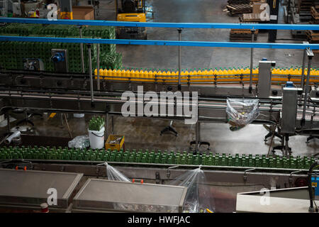 High angle view of bottles on production lines in juice factory - Stock Photo