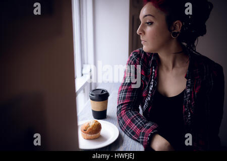 Thoughtful woman looking through window with cupcake and coffee cup on table in café - Stock Photo