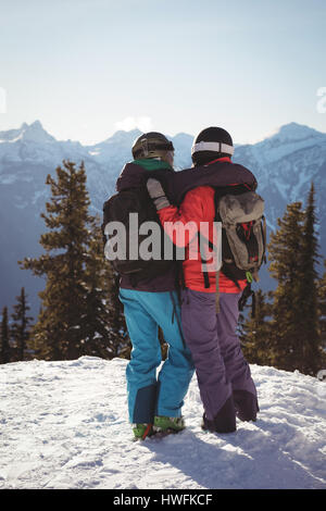 Rear view of two skiers standing together with arm around on snow covered mountain - Stock Photo