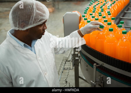 High angle view of serious male worker examining bottles in juice factory - Stock Photo