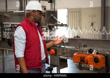 Confident male operator monitoring bottles on production line in juice factory - Stock Photo