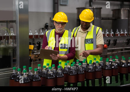 Male workers discussing in juice factory - Stock Photo