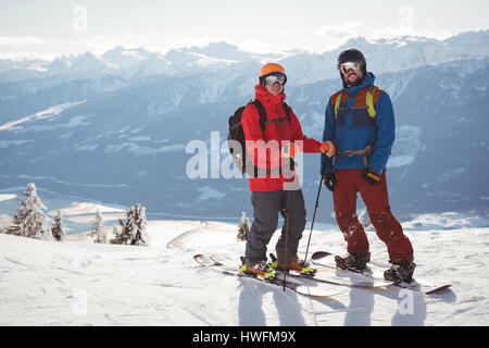 Two skiers standing together on snow covered mountain during winter - Stock Photo