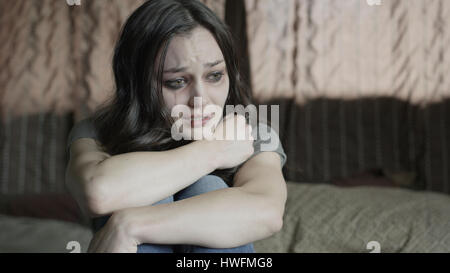 Sad battered woman holding her knees and crying on bed - Stock Photo