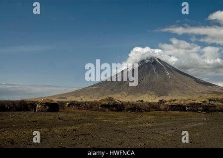 Maasai Village at the foot of Mountain of God (Ol Doinyo Lengai), Lake Natron, Tanzania. - Stock Photo