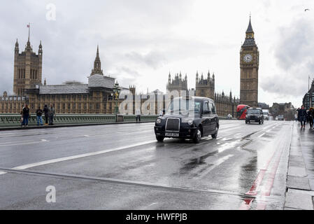 London, UK.  21 March 2017.  The Houses of Parliament are seen, as people pass over Westminster Bridge, on the day - Stock Photo