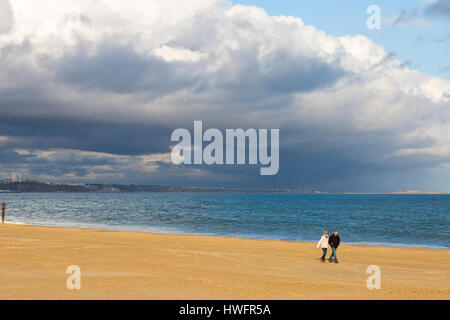 Poole, Dorset, UK. 20 March 2017. UK weather: visitors enjoy the evening sunlight with stormy skies overhead at - Stock Photo
