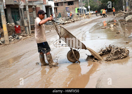 Lima, Peru. 20th Mar, 2017. A man cleans the mud from a flooded road in Huachipa, Lima province, Peru, on March - Stock Photo