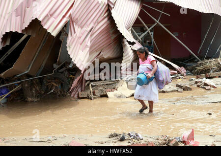 Lima, Peru. 20th Mar, 2017. A woman walks on a flooded road in Huachipa, Lima province, Peru, on March 20, 2017. - Stock Photo