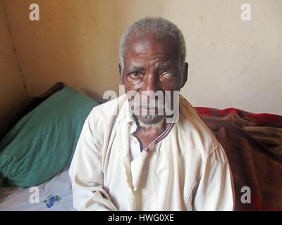 World War II veteran Stephen Kayeb sits on his bed at his home in Kigusa, Uganda, on February 05, 2017. Ugandan - Stock Photo
