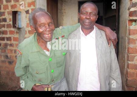 World War II veteran Elismus Katende (l), wearing his old uniform, shares a lugh with his grandson in Mugomba village, - Stock Photo