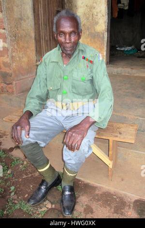 World War II veteran Elismus Katende wears his old uniform in Mugomba village, Uganda, on February 21, 2017. Ugandan - Stock Photo