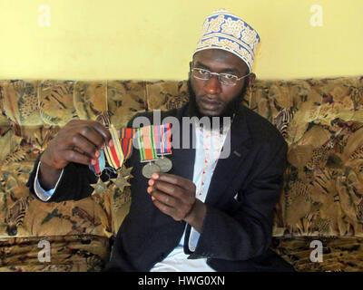 Ramadan Tambula, representative of Uganda Ex-Servicemen·s Association, shows medals of his greatgrandfather Who - Stock Photo