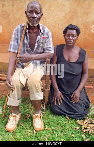 World War II veteran Aloysius Lubega and his Daughter Rovinsa Namatovu are seen in front of his home in Mugomba - Stock Photo