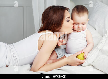 happy beautiful mother kissing her one year old son ,with a green apple, in bed at home - Stock Photo