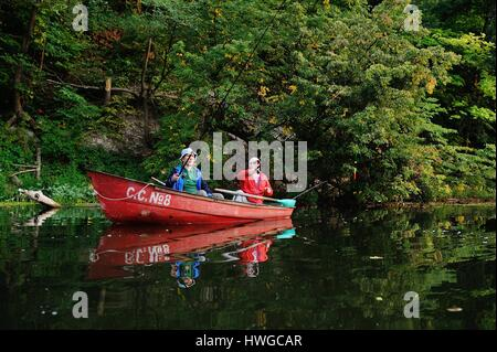Two fishermen in a boat with fishing rods catching fish - Stock Photo
