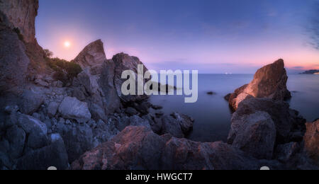 Majestic high rocks and stones glowing by moonlight at the sea. Fantastic night panoramic landscape with mountains, - Stock Photo