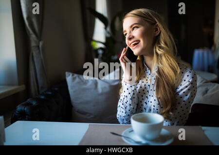happy woman speaking with cell telephone while sitting in coffee shop during morning breakfast - Stock Photo
