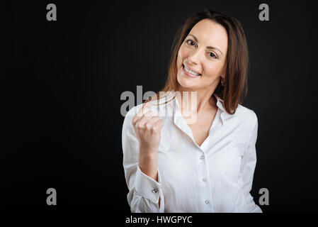 Successful young brunette making fist - Stock Photo