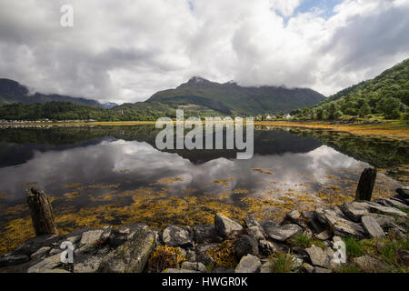 Reflections of Glencoe village in Loch Leven from an old unused jetty, Argyll, Scotland, UK - Stock Photo
