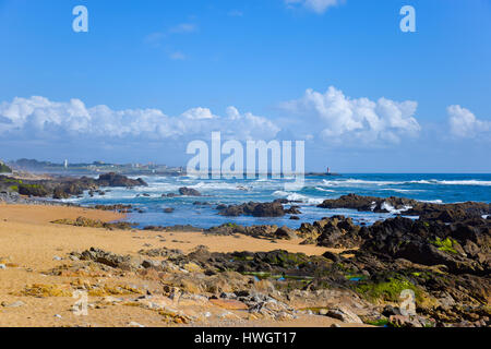Wide sandy beach with many beach rocks, clean blue sea and lovely sky as a background - Stock Photo