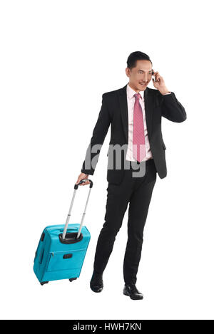 Business man walking with suitcase and talking via cellphone isolated over white background - Stock Photo