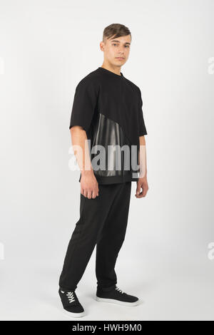 Young muscular man wearing black clothes and sneakers isolated on white background - Stock Photo
