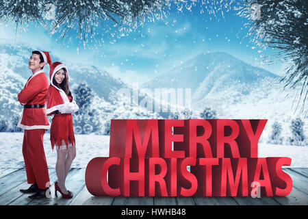 Asian couple in santa claus costume posing on merry christmas text. Christmas couple concept - Stock Photo