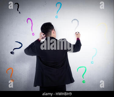 Business man write question mark on the wall. He dont know what to write - Stock Photo
