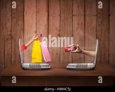 Hand out from computer carry shopping bag, the other show credit card. Online shopping conceptual - Stock Photo