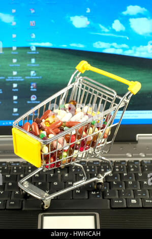 Cart on keyboard with medicine and pills, shopping carts on a computer keyboard with drugs and tablets purchase, - Stock Photo