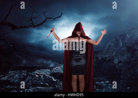 Scary portrait of an asian witch woman covering his face holding a sharp knife bathed in the blood - Stock Photo
