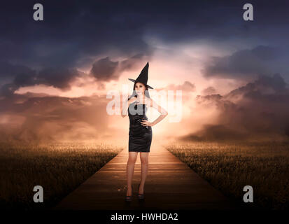 Beautiful asian witch woman with black hat on the meadow - Stock Photo