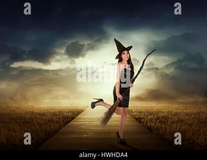 Beautiful asian witch woman with black hat holding broom on the meadow - Stock Photo