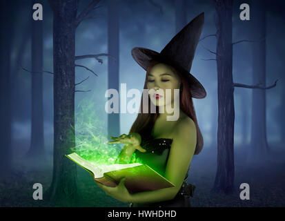 Beautiful asian girl wearing witch cloth reading spell in the book on the forest at night - Stock Photo