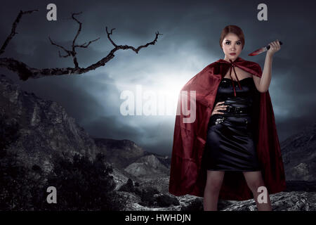 Beautiful asian witch woman holding bloody knife in the night, horror situation. Halloween concept image - Stock Photo
