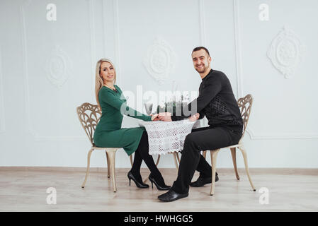 love sitting at the table couple man and woman with wineglasses on white background in the restaurant. valentines - Stock Photo