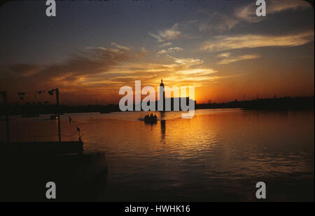 The sun sets silhouetting the Florida Pavilion bell tower and ferry boats on Fountain Lake at the 1939-40 World's - Stock Photo