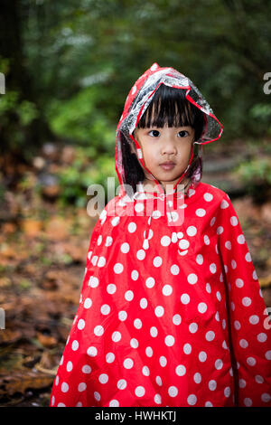 Asian Chinese little girl wearing raincoat in the tropical rain forest alone. - Stock Photo