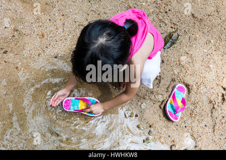 Asian Chinese little girl washing sandals at riverbank alone. - Stock Photo