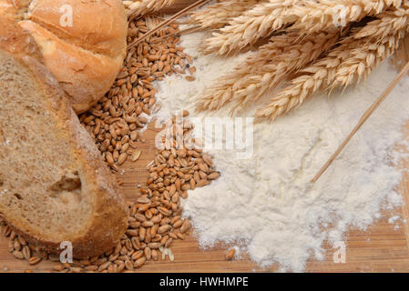 Grains, wheat ears, flour, bread and bagel on a wooden table. Concept of making food from cereals, raw material - Stock Photo