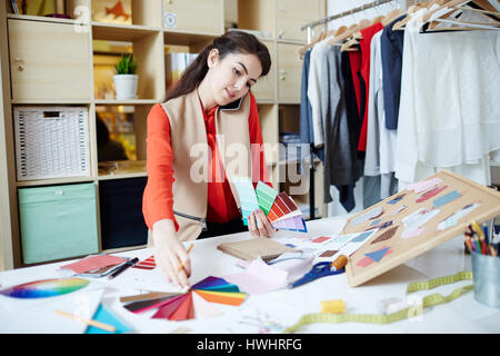 Confident designer speaking on mobile phone while choosing colors from palette - Stock Photo
