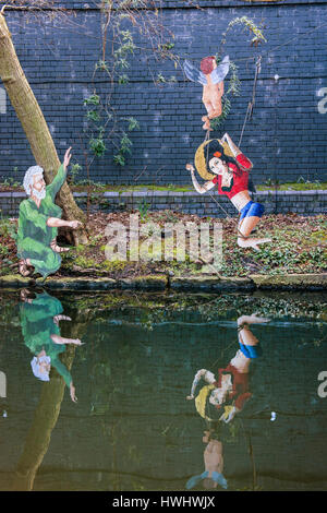 Regents canal  tow path with Amy Winehouse graffiti with cherub,and grey haired man in green - Stock Photo