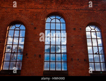 three arched victorian windows showing clouds and sky - Stock Photo