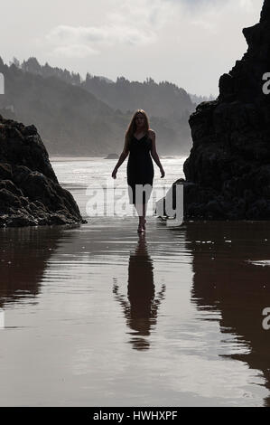 A woman standing in water on the Oregon coast. - Stock Photo