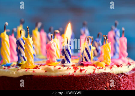 closeup of a cake with some unlit candles and just one lit candle after blowing out the cake - Stock Photo