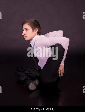 Extraordinary gymnast on a black background. The man with no bones. Studio photography of circus performers - Stock Photo